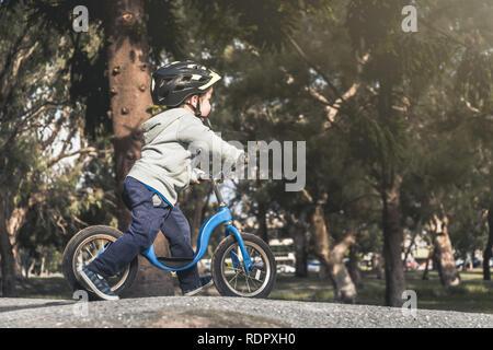 Australian kid riding his balance bike and wearing helmet in the park, South Australia - Stock Photo