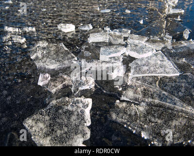 Small chunks of ice on a thinly frozen water surface - Stock Photo