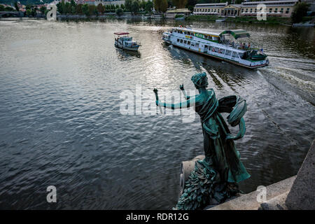 PRAGUE, CZECH REPUBLIC - AUGUST 27, 2015: Tour boats sail and pass by torch bearing bronze female figure statue with patina, Cech Bridge on Vltava - Stock Photo