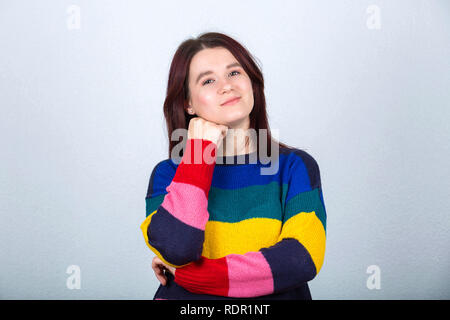 Thoughtful casual young woman holding hand under chin wearing colorful sweater looking to camera isolated over grey background. - Stock Photo