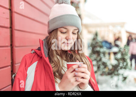 Young girl in a red jacket, warm hat, in city in winter. He holds a cup of coffee or hot tea in his hands and warms up in cold weather. The concept of pleasure and relaxation in the fresh air. - Stock Photo