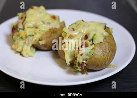 A closeup of two baked potatoes filled with some bacon, chives, sour cream and cheese. Delicious homemade treat served from a white plate. Enjoy! - Stock Photo