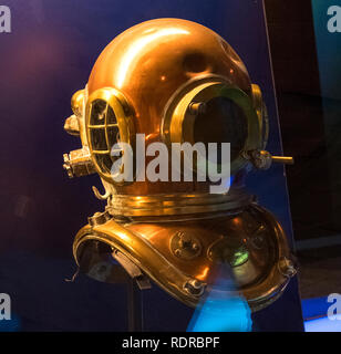 Cherbourg, France - August 26, 2018: Copper diving helmet in the maritime museum La Cite de La Mer or City of the Sea in Cherbourg, Normandy, France - Stock Photo