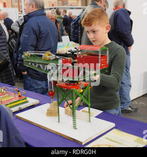 Alexandra Palace, London, UK. 18th Jan 2019. A boy playing with a Meccano crane at the London Model Engineering Exhibition, Alexandra Palace, London.  The London Model Engineering Exhibition is now in its 23rd year, and attracts around 14,000 visitors.   Credit: Michael Preston/Alamy Live News - Stock Photo