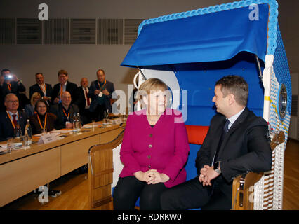 Rostock, Germany. 19th Jan, 2019. Chancellor Angela Merkel (CDU) sits with the state chairman of the CDU Mecklenburg-Western Pomerania, Vincent Kokert, in a beach chair which she received as a gift at the state party conference of the CDU Mecklenburg-Western Pomerania. The CDU Mecklenburg-Western Pomerania will meet in the city hall for their 34th state party conference. Credit: Danny Gohlke/dpa/Alamy Live News - Stock Photo