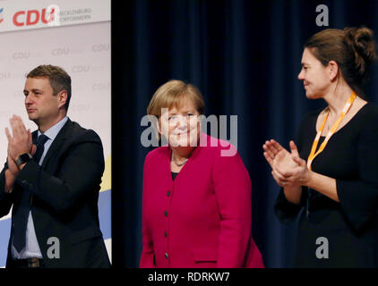 Rostock, Germany. 19th Jan, 2019. Vincent Kokert (l), state chairman of the CDU Mecklenburg-Western Pomerania, and Martina Liedtke (CDU, r) applaud Chancellor Angela Merkel (CDU) after her speech at the state party conference of the CDU Mecklenburg-Western Pomerania. The CDU Mecklenburg-Western Pomerania will meet in the city hall for their 34th state party conference. Credit: Danny Gohlke/dpa/Alamy Live News - Stock Photo