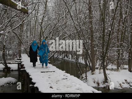 Srinagar, Indian-controlled Kashmir. 19th Jan, 2019. Girls walk on a snow-covered footbridge after fresh snowfall in Srinagar city, the summer capital of Indian-controlled Kashmir, Jan. 19, 2019. Credit: Javed Dar/Xinhua/Alamy Live News - Stock Photo