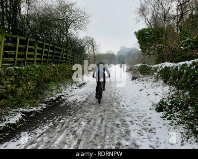 UK Weather: mountain bikers enjoying the snow conditions along the High Peak Trail, Black Rocks, Bolehill, Derbyshire, Peak District National Park Credit: Doug Blane/Alamy Live News - Stock Photo