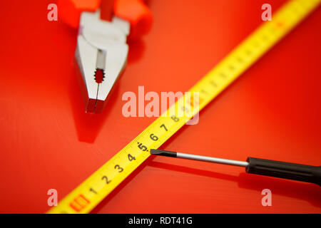 A tape measure, a screwdriver-tap and pliers lie on a red polished surface in a car repair shop. Performance of work. - Stock Photo