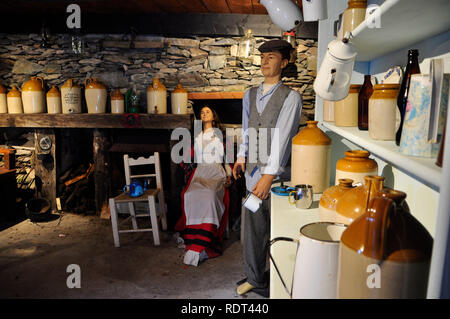 Interior display in a cottage in the Kerry Bog Village.Showing many earthenware jugs and containers and other pots and pans.Bare stone walls - Stock Photo