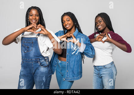 Portrait of three beautiful african women smiling in love showing heart symbol and shape with hands over white isolated background. Romantic concept. - Stock Photo