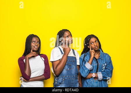 Portrait of group of three beautiful african women with hand on chin thinking about question, pensive expression over yellow background. Smiling with  - Stock Photo