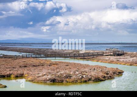 Boardwalk crossing the salt ponds and marshes of Alviso Marsh, Don Edwards National Wildlife Refuge, south San Francisco bay, San Jose, California - Stock Photo
