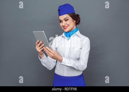 Professional Occupation. Stewardess standing isolated on grey with digital tablet answering video call happy - Stock Photo