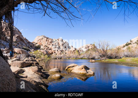 Rock boulders reflected in the calm waters of Barker Dam, Joshua Tree National Park, south California - Stock Photo