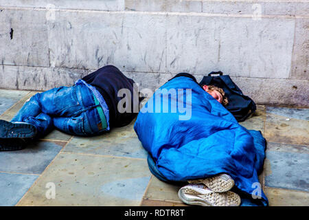 London, UK. Two men sleeping on the streets of the capital - one in a sleeping bag; one without. - Stock Photo