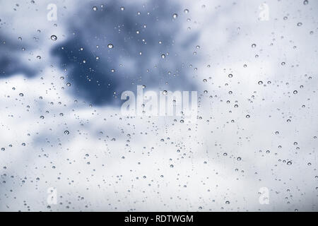 Raindrops on the windshield; in the background white clouds and a spot of blue sky, California - Stock Photo