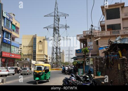 Street view of metal electricity pylon and high voltage power lines in Jaipur, Rajasthan, India - Stock Photo