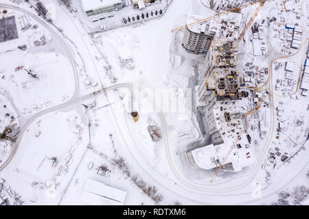 city construction site covered with white snow. building of new apartments in winter, aerial view - Stock Photo