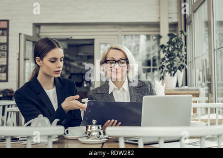Female lawyer speaking with her secretary sitting in restaurant - Stock Photo
