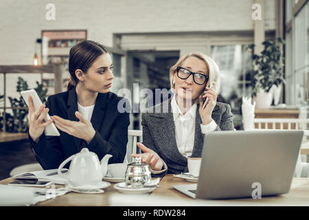 Busy businesswoman wearing white blouse and grey jacket - Stock Photo
