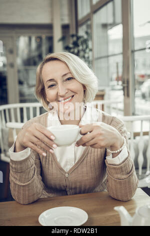 Beaming woman wearing white blouse and sweater drinking tea - Stock Photo