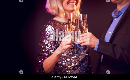 Image of happy couple with champagne glasses with champagne on black background - Stock Photo