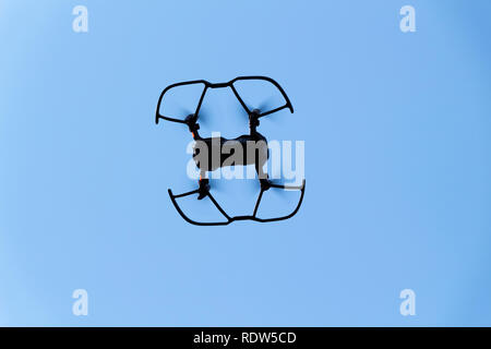 The black quadrupter flies against the blue sky. - Stock Photo