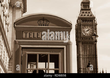 A typical British telephone box on the sidewalk with the famous Elizabeth Tower (Big Ben) in the background - London, UK - Stock Photo
