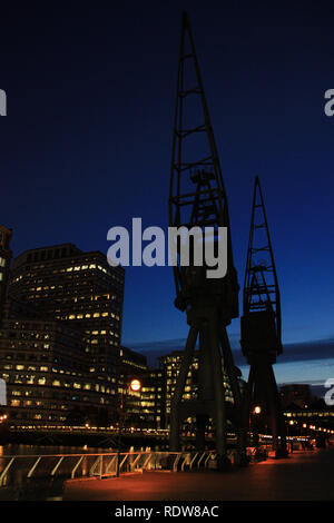 Silhouettes of two industrial cranes at the pier of Canary Wharf in London, United Kingdom - Stock Photo