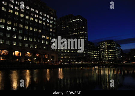Night view of office towers reflecting in the water of the river Thames at Canary Wharf, London, United Kingdom - Stock Photo