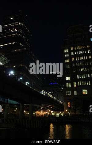 Night view of a London Underground train passing a bridge over the Thames river at Canary Wharf in London, United Kingdom - Stock Photo