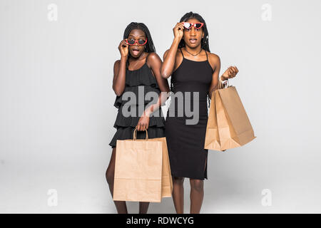 Portrait of shocked young two african ladies friends standing over grey wall and posing with shopping bags. - Stock Photo
