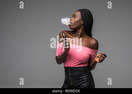 African woman smoking or vaping e-cig or electronic cigarette holding a mod with a lot of clouds on black background - Stock Photo