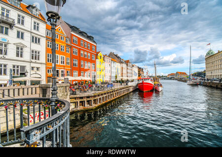 Tourists sightsee, shop and dine at sidewalk cafes on an autumn day on the 17th century waterfront canal Nyhavn in Copenhagen, Denmark. - Stock Photo