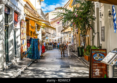Athens, Greece - September 22 2018: Tourists walk the streets lined with souvenir shops and outdoor sidewalk cafes in the touristic Plaka section - Stock Photo