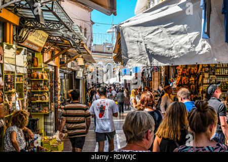 Athens, Greece - September 22 2018: Tourists walk the streets lined with souvenir shops and cafes in the touristic Plaka section of Athens, Greece - Stock Photo