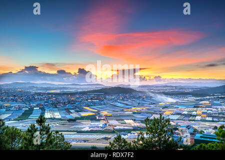 Sunset scene in valley with greenhouses to plant flowers and vegetables. The moment when the sun go down to horizon, the rays of sunlight were shining - Stock Photo