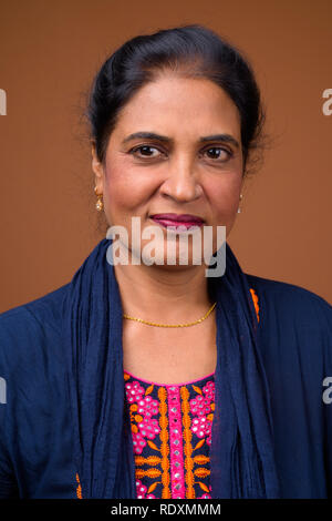 Face of beautiful Indian woman against brown background - Stock Photo