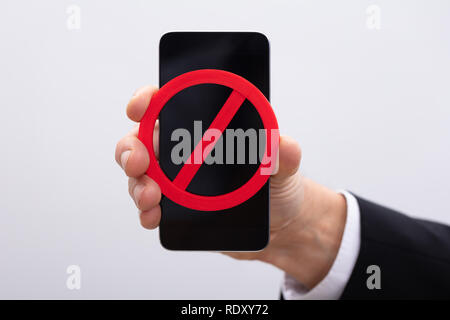 Business Person Showing Red No Sign On Mobile Phone - Stock Photo