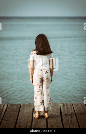 Rear view of a girl standing on pier by the sea - Stock Photo