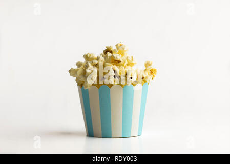 Popcorn in a small paper bucket on white background - a concept - Stock Photo