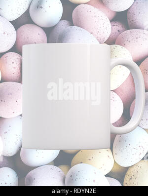 White blank mug on a background of mini chocolate eggs. Perfect for businesses selling mugs, just overlay your quote or design on to the image. - Stock Photo