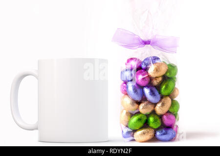 White Mug Mockup - Easter theme. Bag of Easter mini chocolate eggs next to a blank white mug. Perfect for businesses selling mugs, just overlay your q - Stock Photo