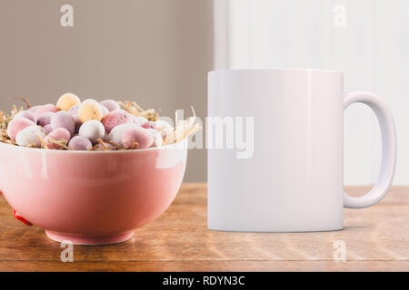 Pretty pink bowl with mini chocolate eggs in, next to a white coffee mug. Perfect for businesses selling mugs, just overlay your quote or design on to - Stock Photo