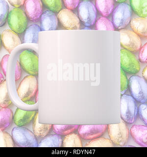 White Mug Mockup on a background of mini chocolate eggs. Easter theme. Perfect for businesses selling mugs, just overlay your quote or design on to th - Stock Photo