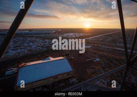 The sun sets behind a snow covered desert in Santa Teresa, New Mexico near El Paso - Stock Photo