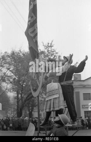 It was demonstration on 1-st May of 1978. Motorcyclist carries symbol of the Soviet era-the worker and the peasant. They stand upright on pedestal made directly on sidecar. The man and woman are specially dressed in appropriate clothes. They hold the flag of the USSR and metal hammer and sickle. The motorcyclist rides ahead of long column. The procession passes through the Central square of small town. Citizens with a sinking heart are look at the living symbol of communism. - Stock Photo