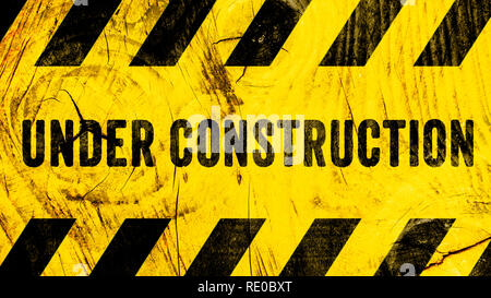 Under construction warning sign text with yellow black stripes painted on wood wall plank texture wide banner panorama background. Concept do not ente - Stock Photo