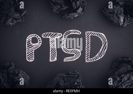 Post Traumatic Stress Disorder. Abbreviation PTSD on a black background and black crumpled paper balls around it. Close up. - Stock Photo